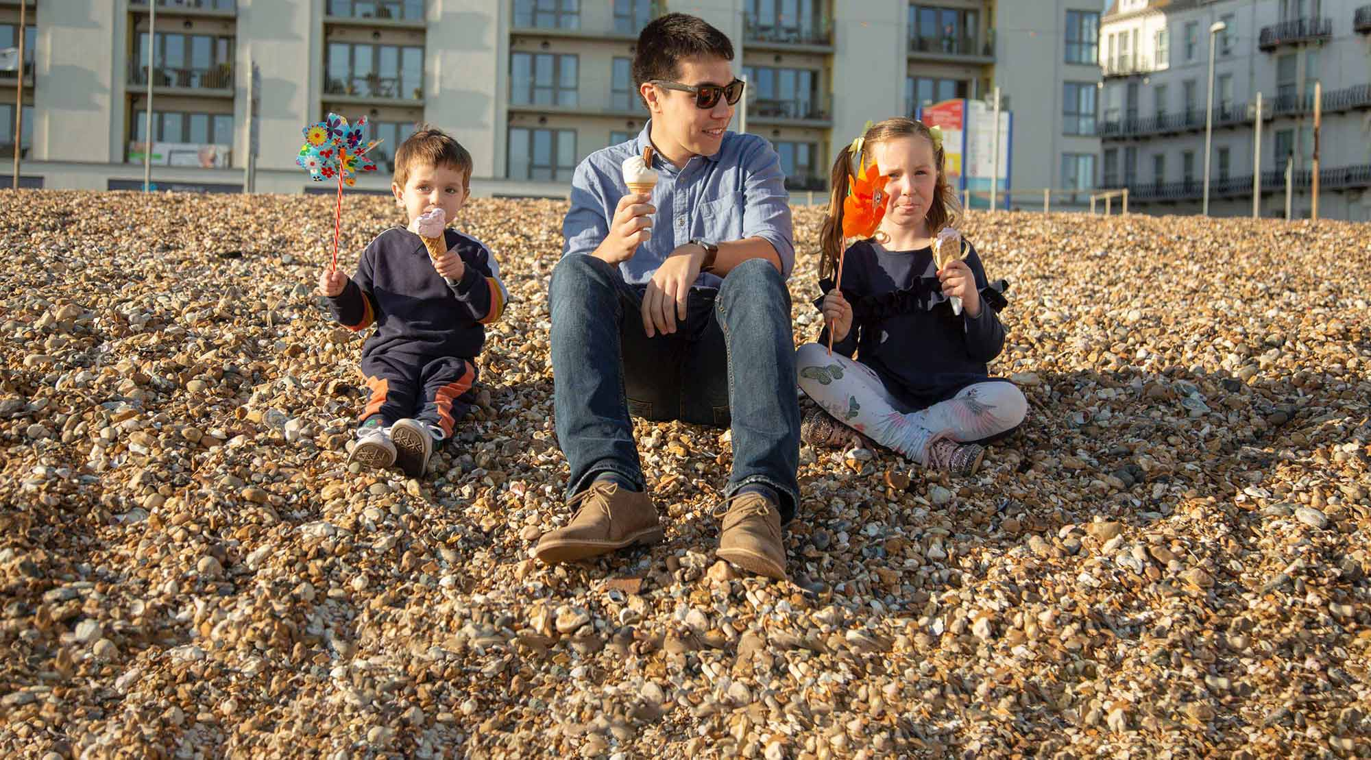 Male foster carer sat on Southsea beach with young foster children eating ice cream>